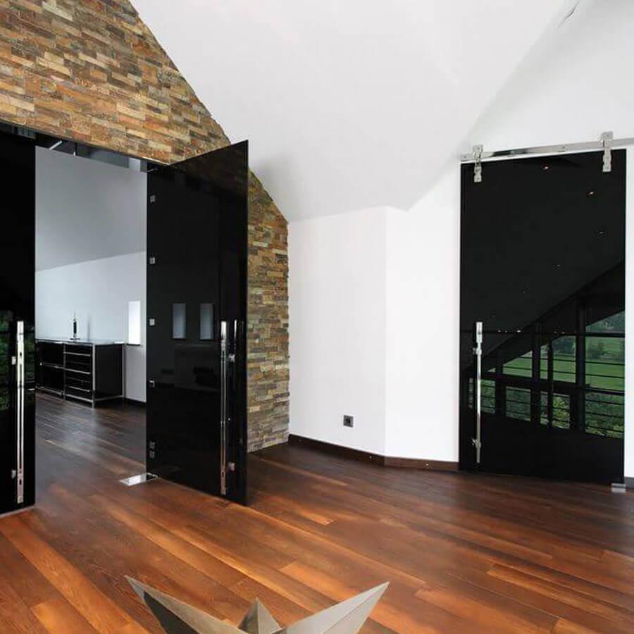 Schwarze Schiebetür mit Holz- & Steinelementen
